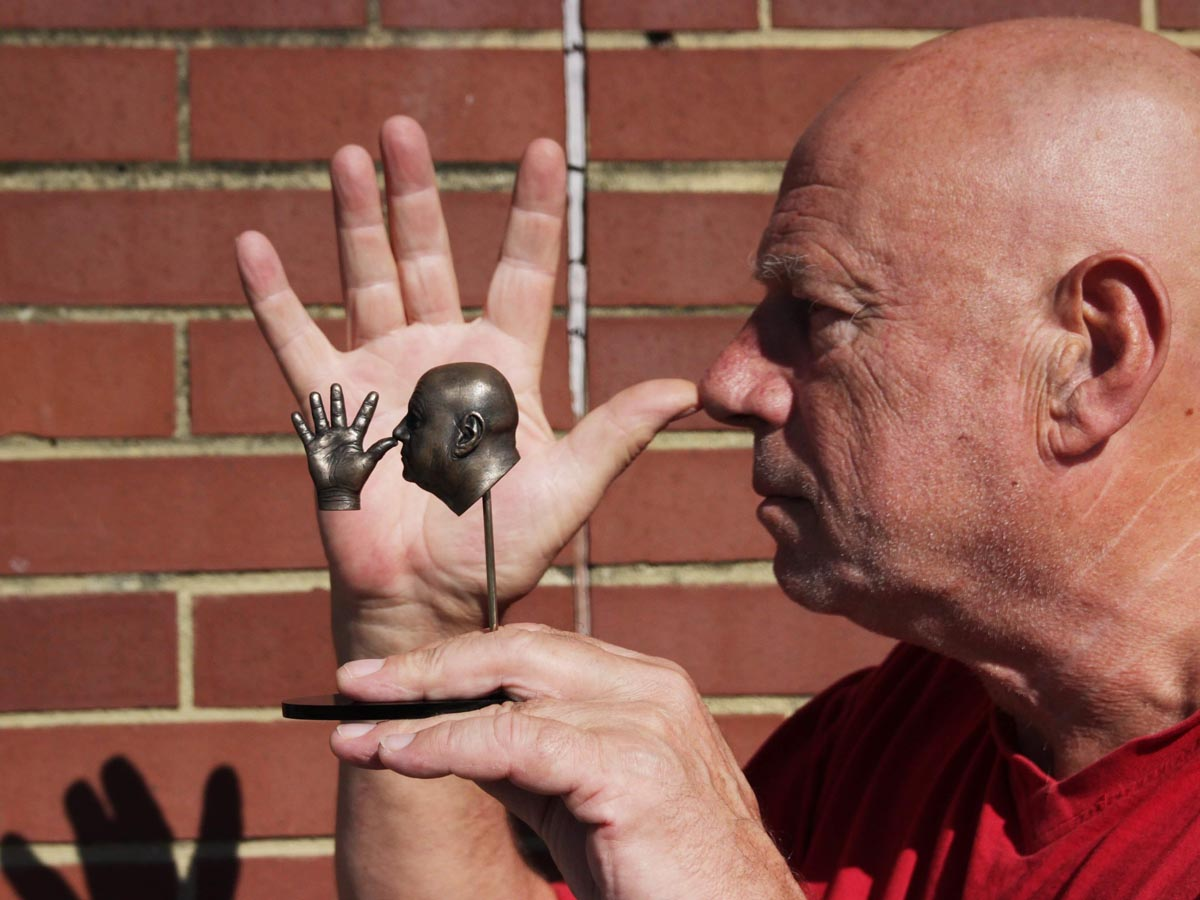 Neil Innes thumbing his nose with a miniature sculpture of him in the Ego Warrior pose