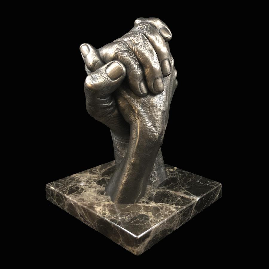 adult hands handclasp cast in bronze