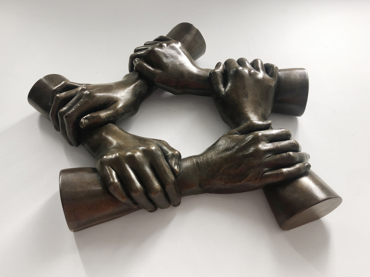 5 hands holding each other by the forearm in a hexagonal ring cast in bronze